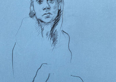 M-J Kelley's drawing of Rebecca. A portrait of her face with loose styling of shoulders and arms crossed at mid arm. Drawn on Canson / Ingres medium blue paper with charcoal and a touch of white highlight..